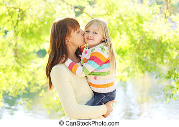 Happy mother kissing daughter child in summer day