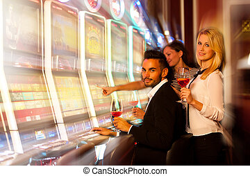 four young people playing slot machines in casino - young...