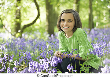 Child and bluebells - young girl sitting in a wood full of...