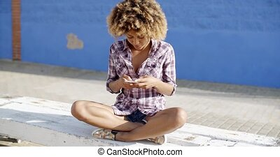 Female Using Mobile Phone On A Road - Young female using...