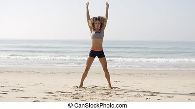 Fit Woman Jumping On The Beach