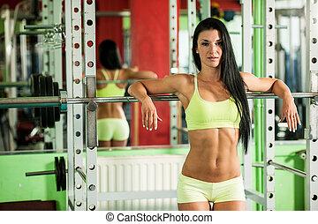 bikini fitness woman leaning on wei - woman in fitness gym...