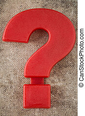 Red plastic question mark on old canvas background