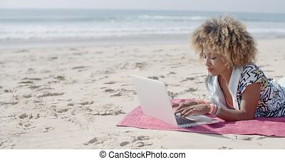 Woman At The Beach Working On A Laptop - Young girl working...