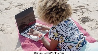 Young Girl Using Computer - Young girl lying on the beach...