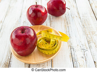 Red apple and yellow tape measure on a wooden table