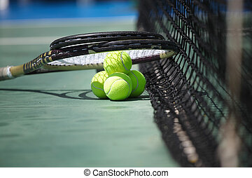 Tennis balls and racquets on court - Tennis balls and...