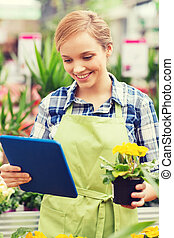 happy woman with tablet pc in greenhouse - people,...