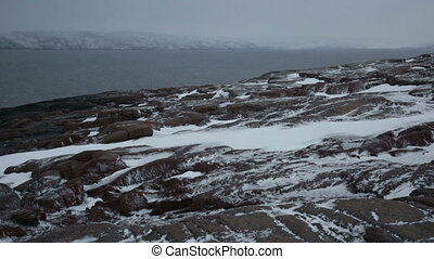 Snow storm on the rocky shores of the Arctic Ocean