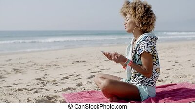 Woman Listening To Music On The Beach - Young woman...