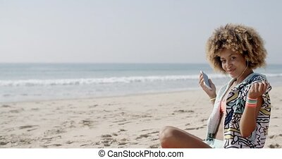 Young Woman With Earphones On The Sea Coast - Young woman...