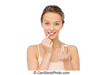 smiling young woman applying lip balm to her lips - beauty,...
