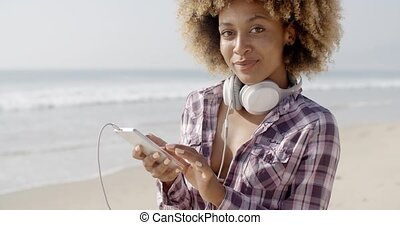 Girl On Beach Listening To Music - Funny young girl on beach...