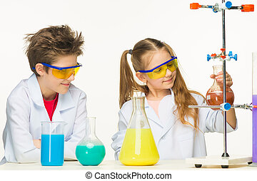 Two cute children at chemistry lesson making experiments on...