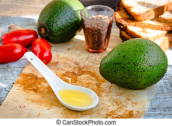 avocado oil in a spoon and fresh green avocado, healthy food
