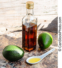 avocado oil in a glass bottle and fresh green avocado,...