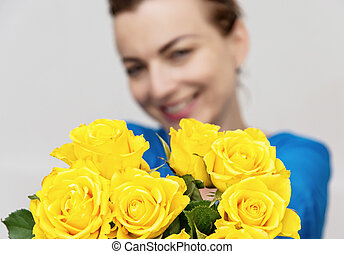 Young smiling brunette posing with the bouquet of yellow...