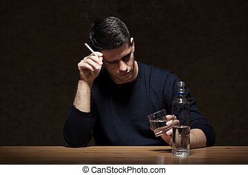 Smoking and drinking - Young man is smoking and drinking...