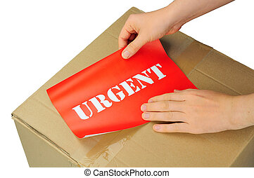urgent delivery - hands placing label on parcel for urgent...