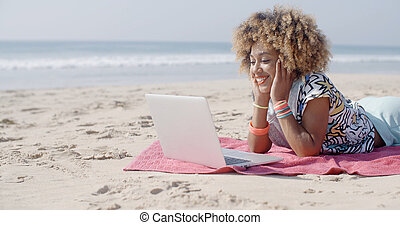 Woman On The Beach Using A Computer - Woman on the beach...