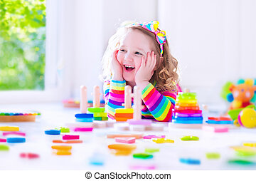 Little girl playing with wooden toy blocks