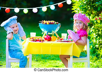 Garden grill party for kids - Children grilling meat. Family...