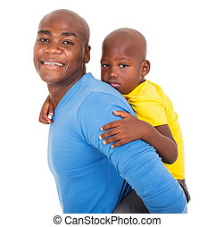 afro american father carrying his son on his back