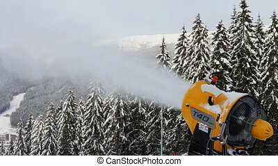 Snow machine gun on a ski slope - Yellow snow cannon stands...