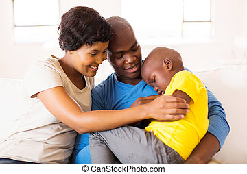young african couple comforting ill son - loving young...