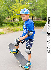 Young Boy Doing Simple Trick on Skateboard - Full Length of...