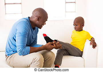 african man taking off son's socks - loving african man...