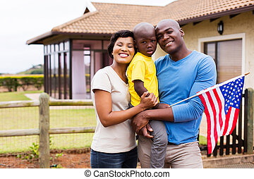 young family holding american flag - portrait of young...
