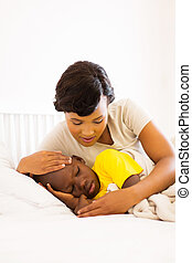 african american mother checking her son temperature -...