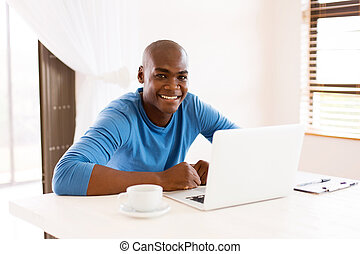 african man using laptop computer - happy african man using...