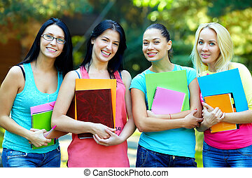 four beautiful college students  posing outside in green park