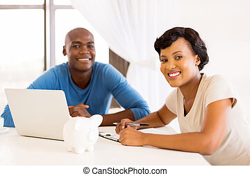 young african couple paying bills - smart young african...