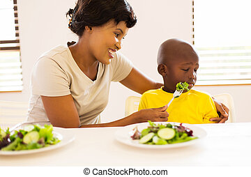 african mother trying to feed her little son green salad -...