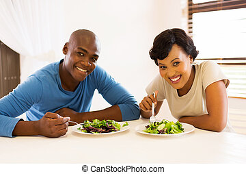 young african american couple eating healthy salad