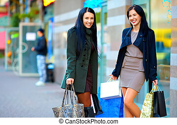 happy girls with shopping bags in city street