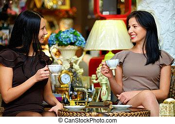 two elegant ladies have a tea break in retro cafe