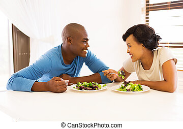 young african couple eating dinner together