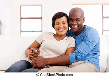 african american couple sitting on sofa at home