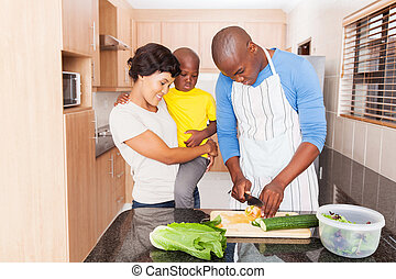 african man making salad for family in home kitchen