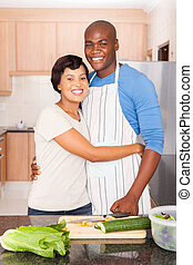 young black couple cooking in kitchen - happy young black...