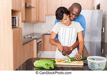 young african couple cooking in kitchen