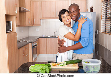 african american couple embracing in kitchen - romantic...