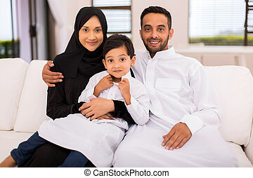 muslim family sitting on the couch - happy muslim family...