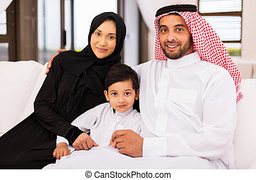 young arabian family sitting on sofa at home