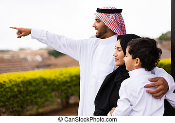 muslim family outside their home pointing