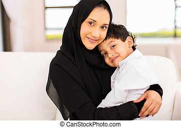 young muslim woman sitting on couch with her son -...